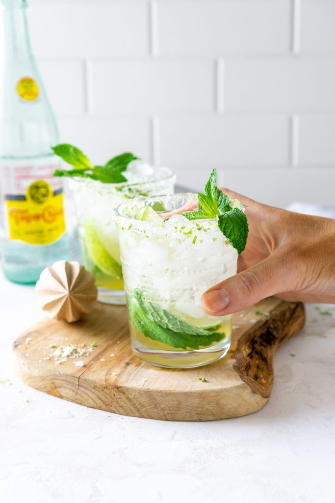 hand holding a mojito on a wood serving tray