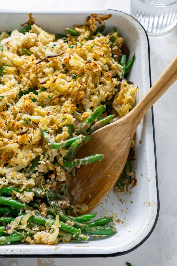 healthy green bean casserole in a white baking dish with a wooden spoon