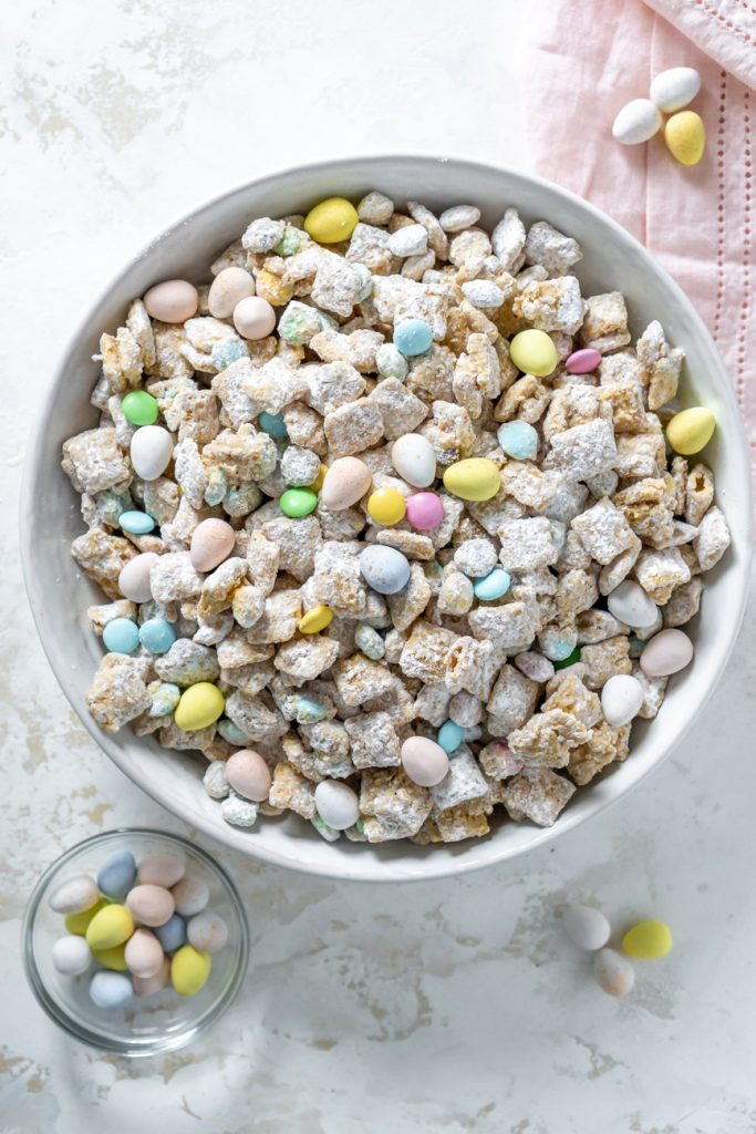 puppy chow in a large white bowl with a pink napkin