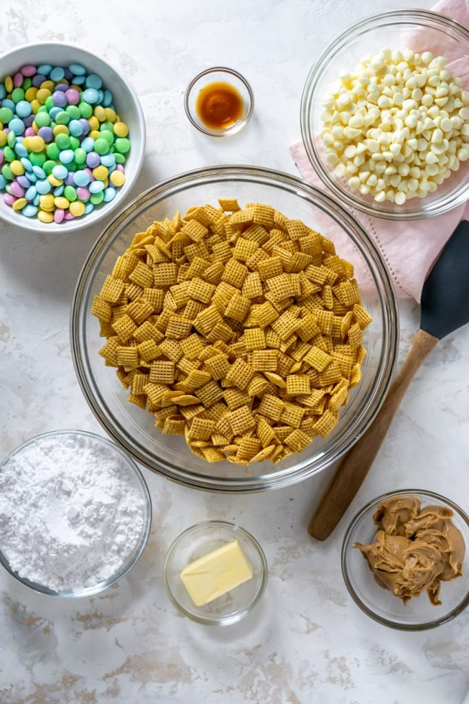 chex mix, m&ms, white chocolate chips, powdered sugar, and butter in small bowls