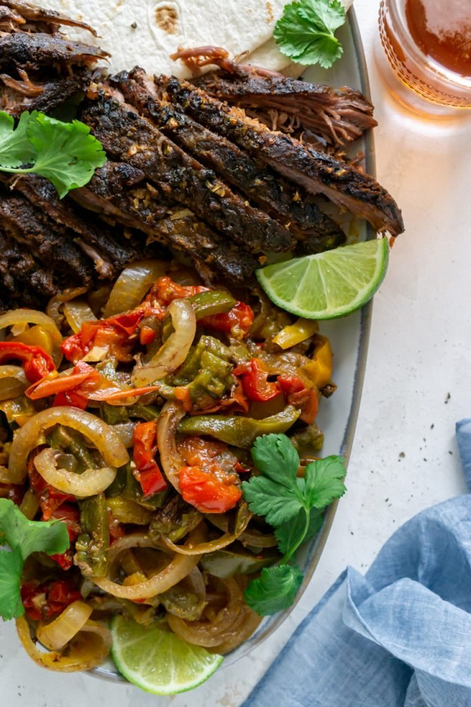 steak fajitas on a serving plate with lime wedges