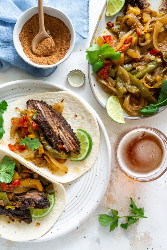 steak fajitas in tortillas on a white plate with beer