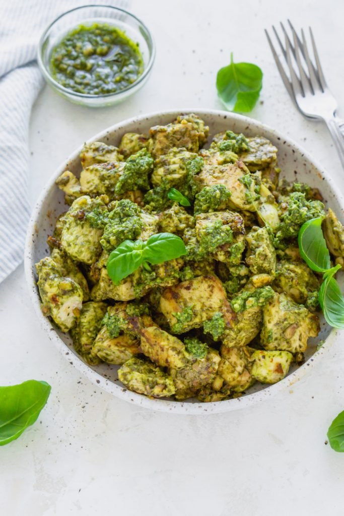 basil pesto chicken in a bowl with two forks