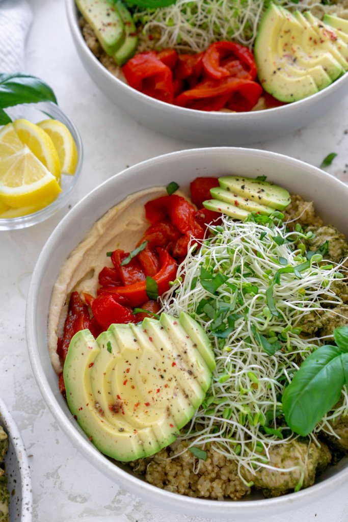 two pesto chicken power bowls with lemon wedges