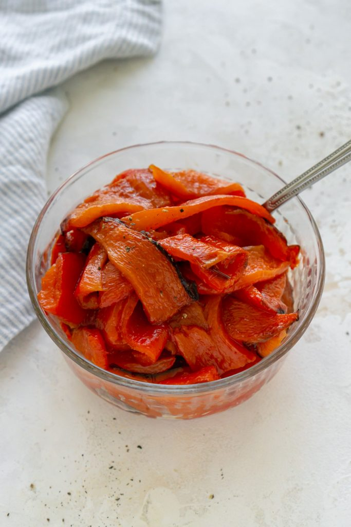 sliced roasted red peppers in a glass bowl with a spoon