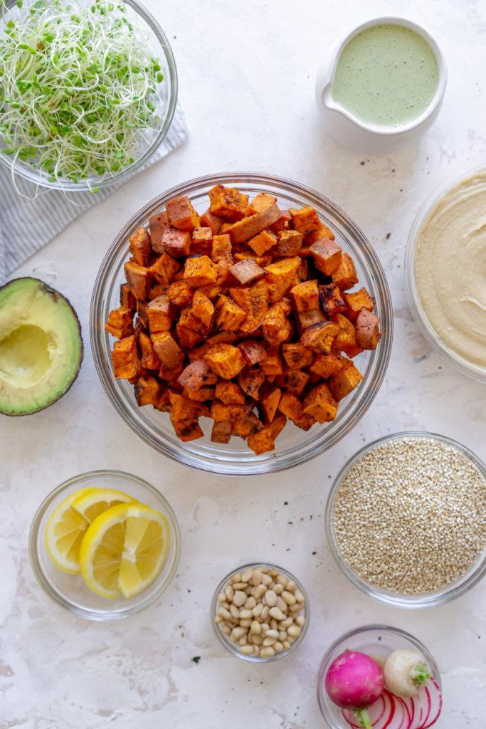 ingredients in bowls: sweet potatoes, avocado, dressing, lemon wedges, sprouts, quinoa
