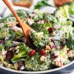 broccoli salad in a bowl with a wooden serving spoon