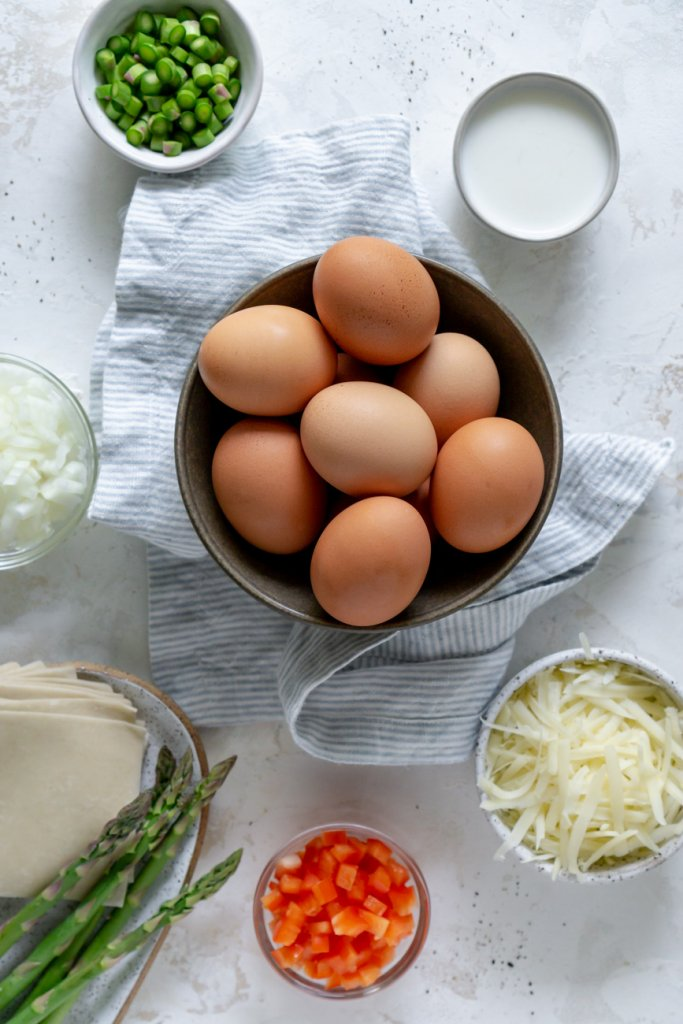 ingredients in small bowls: eggs, peppers, onions, wonton, asparagus, milk