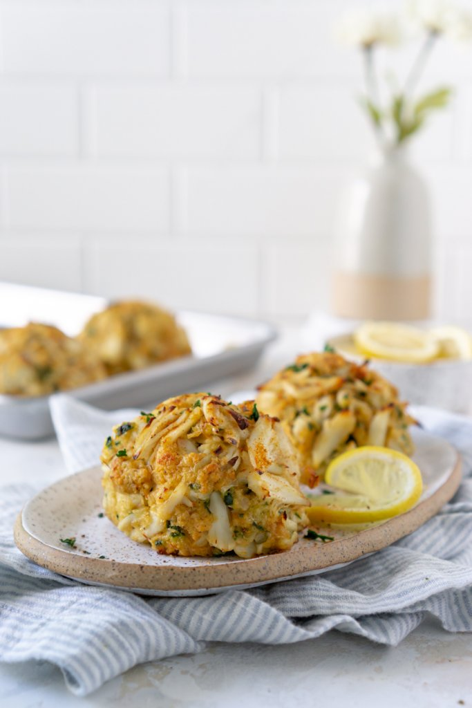 two crab cakes on a plate with a sheet pan and flowers in the background