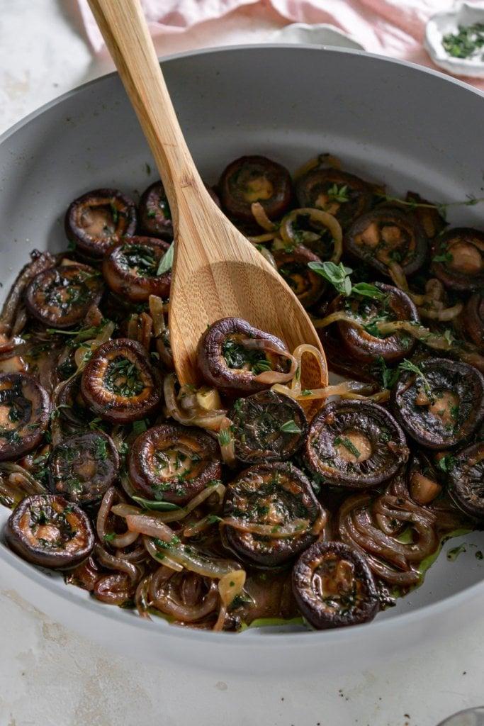 wooden spoon scooping mushrooms in a pan