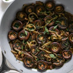 red wine mushrooms in a grey pan with fresh herbs