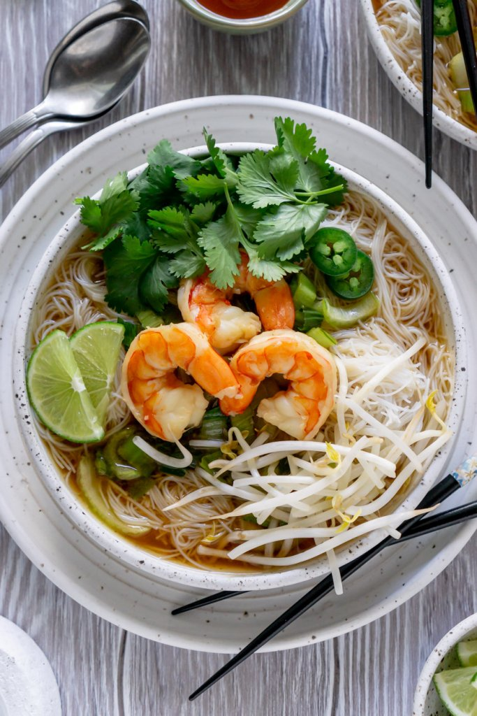 shrimp pho with cilantro, limes, and two spoons