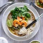 two bowls of shrimp pho noodle soup with chopsticks, sriracha, and limes