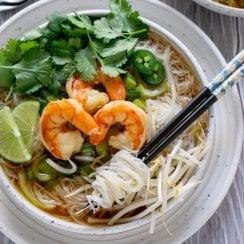 shrimp pho in a white bowl with chopsticks