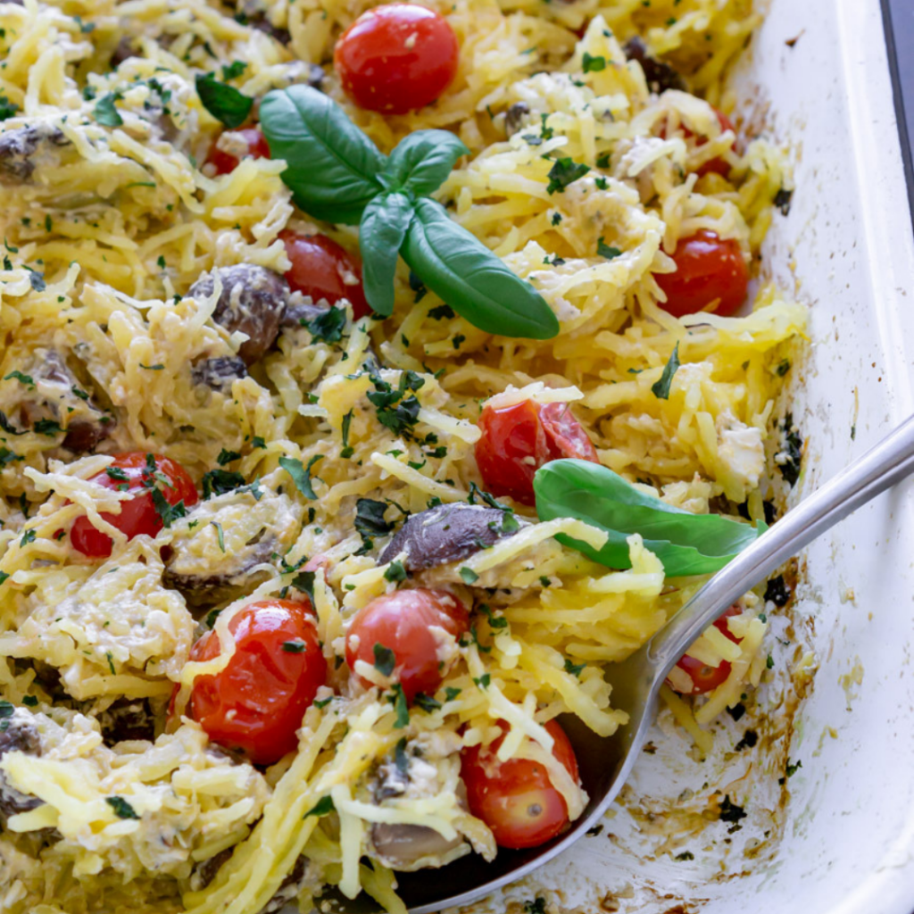 baked spaghetti squash with tomatoes, mushrooms, and feta cheese in a white dish