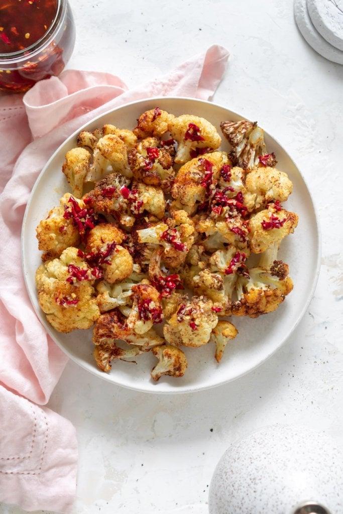 air fryer cauliflower on a plate with chili garlic sauce