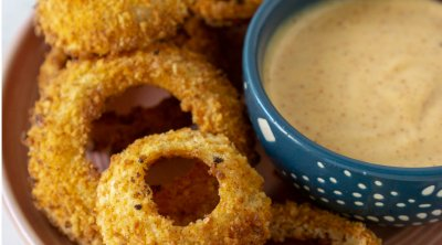 air fryer onion rings on a plate with sauce