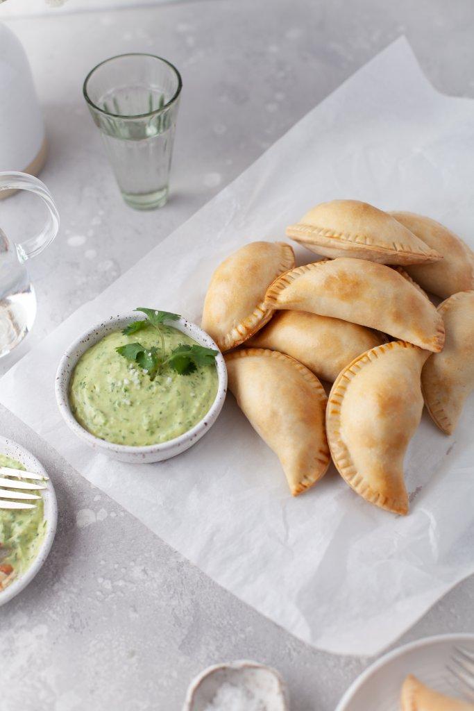 chicken empanadas on parchment paper with green empanada sauce