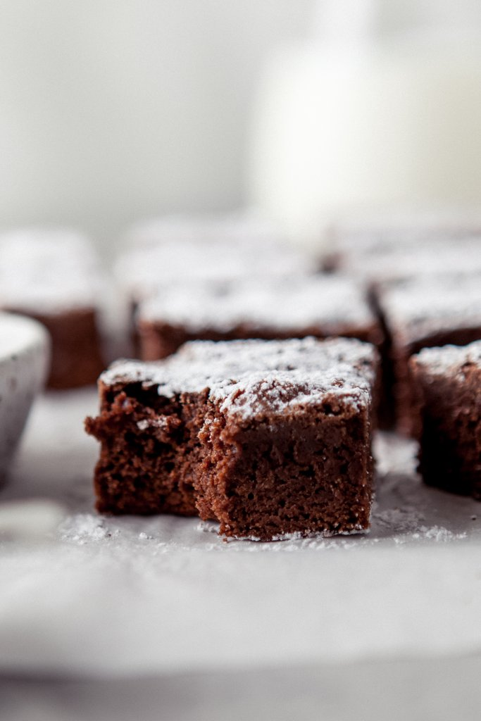 close up of a dark chocolate brownie with a bite taken