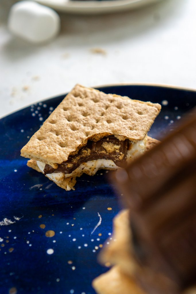 a s'more on a blue plate with a bite taken out