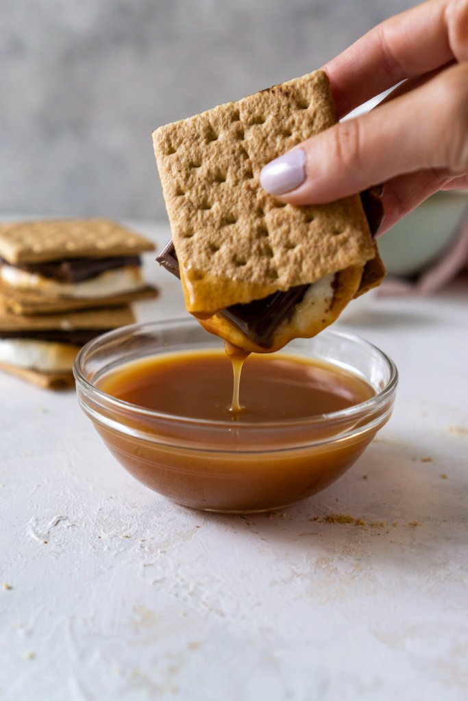 dipping a s'more in caramel sauce
