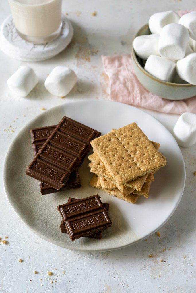 ingredients on a plate: chocolate, graham crackers, marshmallows