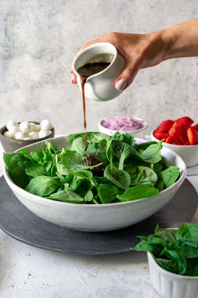 pouring balsamic dressing on spinach in a white bowl