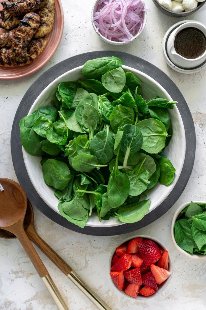 ingredients in separate bowls: spinach, strawberries, red onion, vinaigrette, basil, mozzarella, chicken