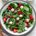 strawberry caprese chicken salad in a large white bowl with dressing to the side