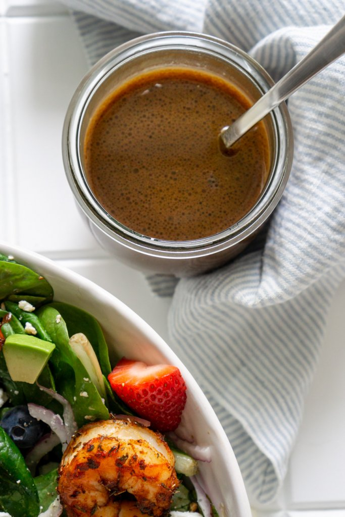 honey balsamic dressing in a glass jar with a silver spoon and a salad