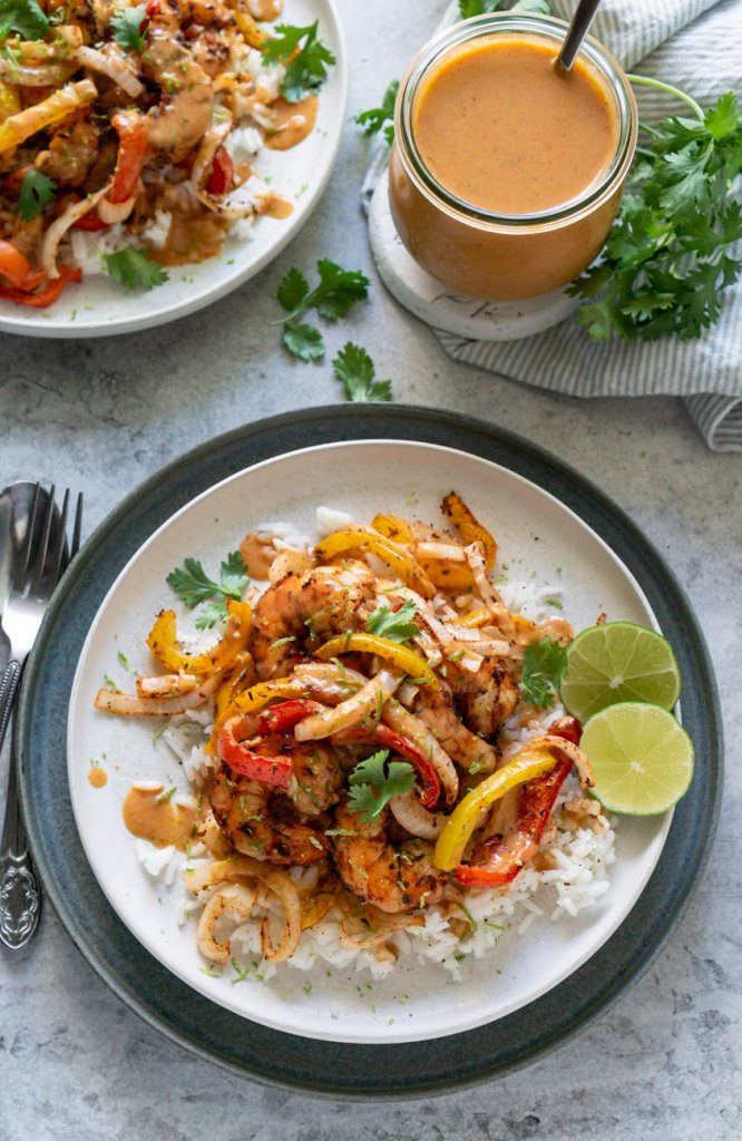 two plates with air fryer shrimp and peppers over rice