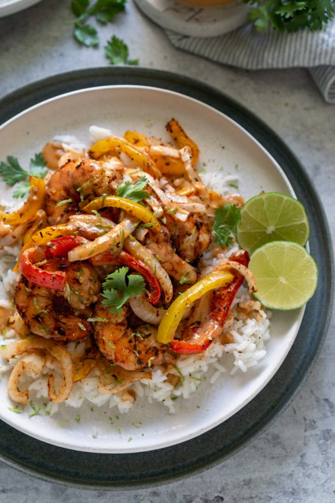 air fryer shrimp and peppers on a white plate with limes