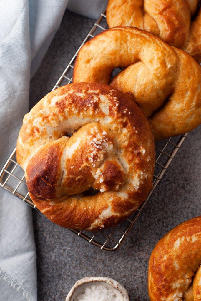 3 homemade soft pretzels on a cooling rack