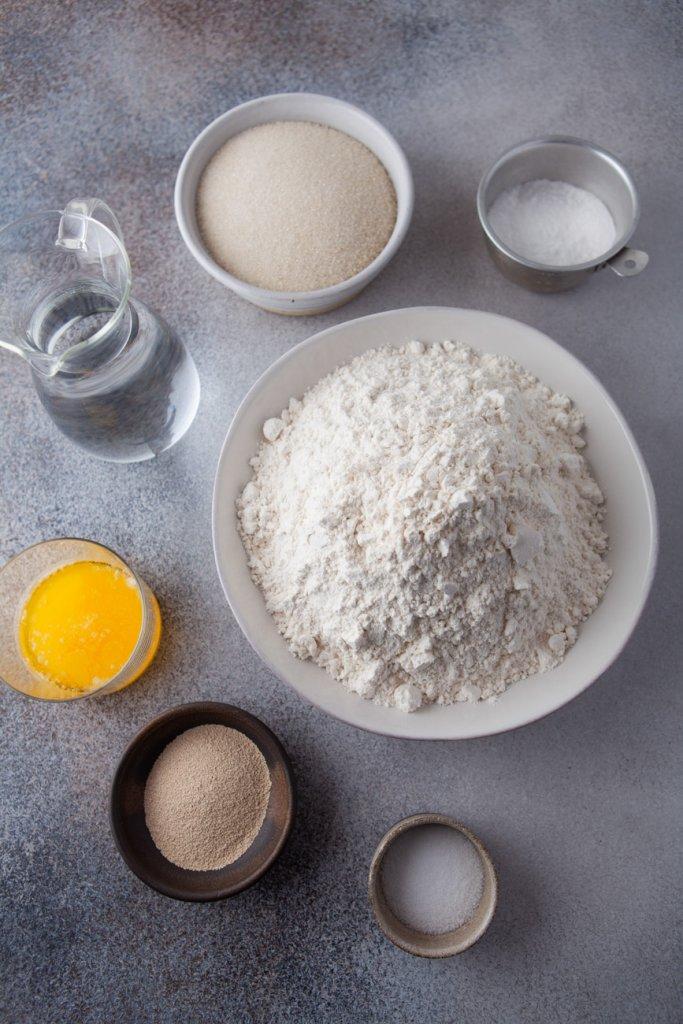 ingredients in bowls: flour, yeast, salt, egg, water