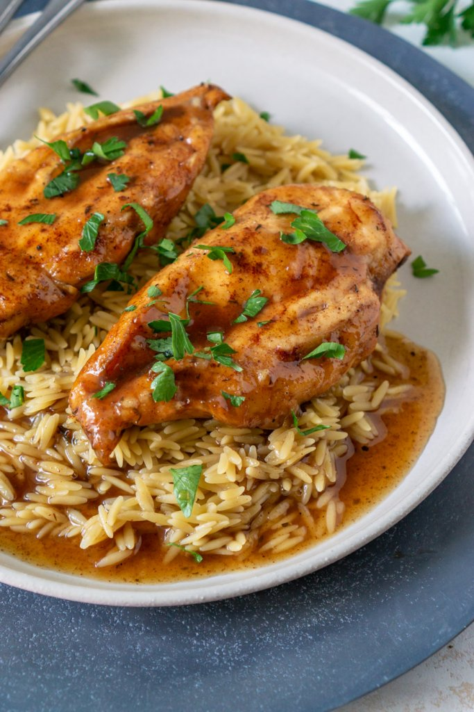 two balsamic chicken breasts on a white plate with orzo