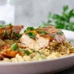 chicken sliced on a plate with orzo