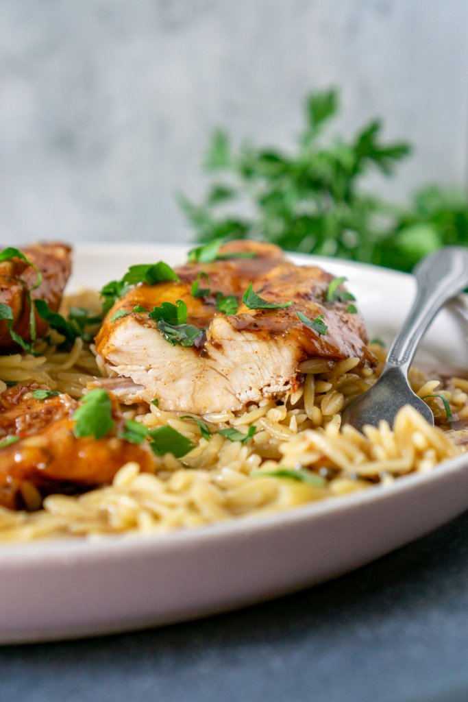 sliced slow cooker balsamic chicken on a plate with orzo and a fork