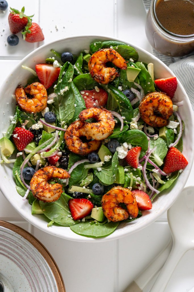 strawberry spinach salad with shrimp in a white bowl