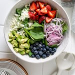 spinach, strawberries, avocado, red onion, blueberries, goat cheese in a salad bowl