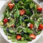 strawberry spinach salad in a large white bowl