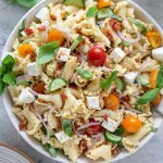 gluten free pasta salad in a serving bowl with basil leaves