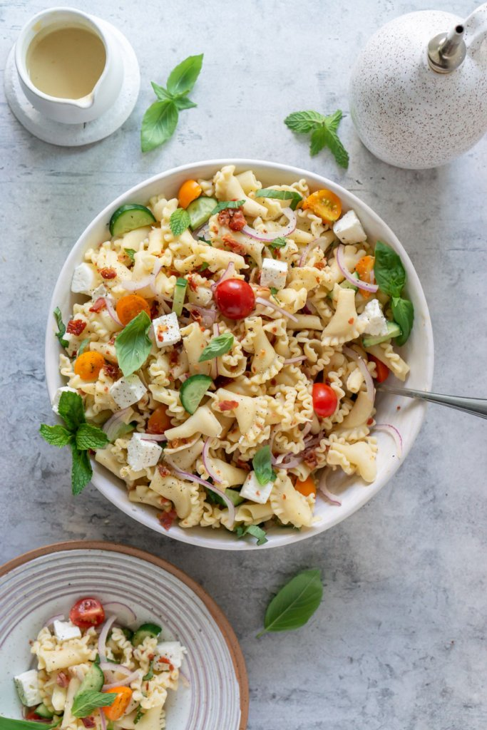 mediterranean gluten free pasta salad in a serving bowl and on a plate