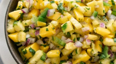 pineapple mango salsa in a brown bowl with a spoon