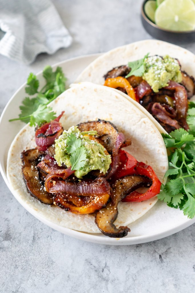 two vegetarian fajitas tacos on a plate with cilantro