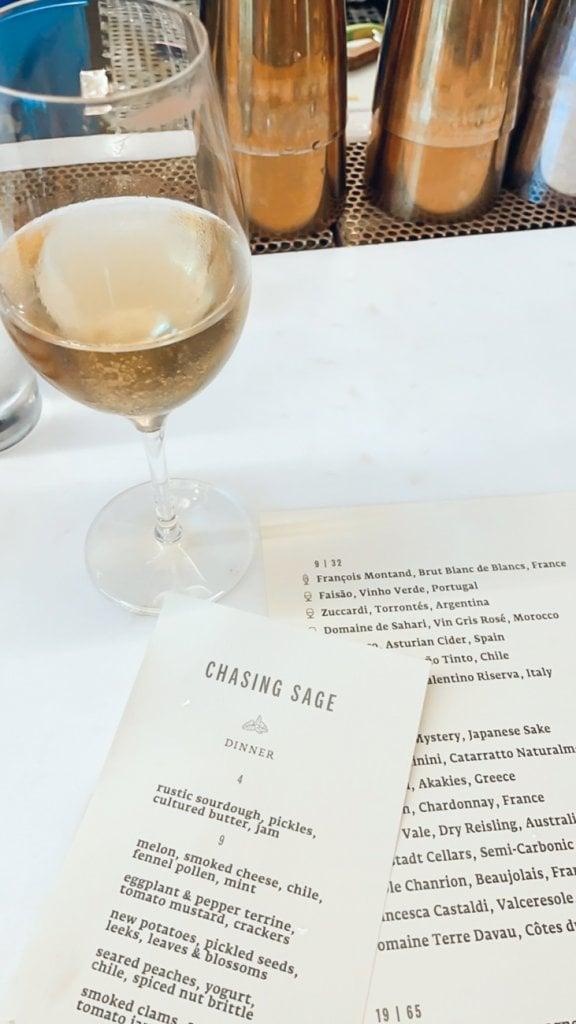 wine glass and menu at chasing sage
