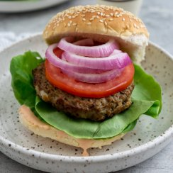 air fry frozen burger on a plate with lettuce, onions, and tomato