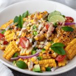 corn salad in a white bowl topped with cilantro and lime wedges