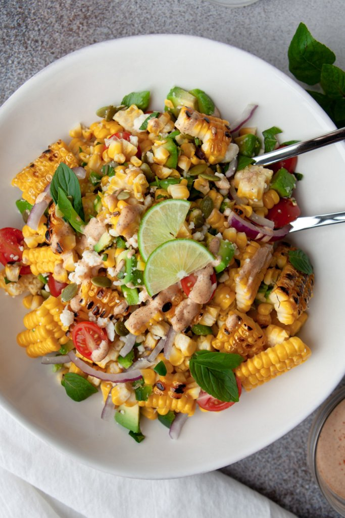 avocado corn salad in a white bowl with lime wedges