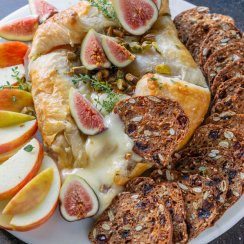 baked brie on a white tray with figs, apples, and crackers