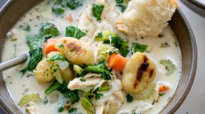 a bowl of chicken gnocchi soup with a piece of bread